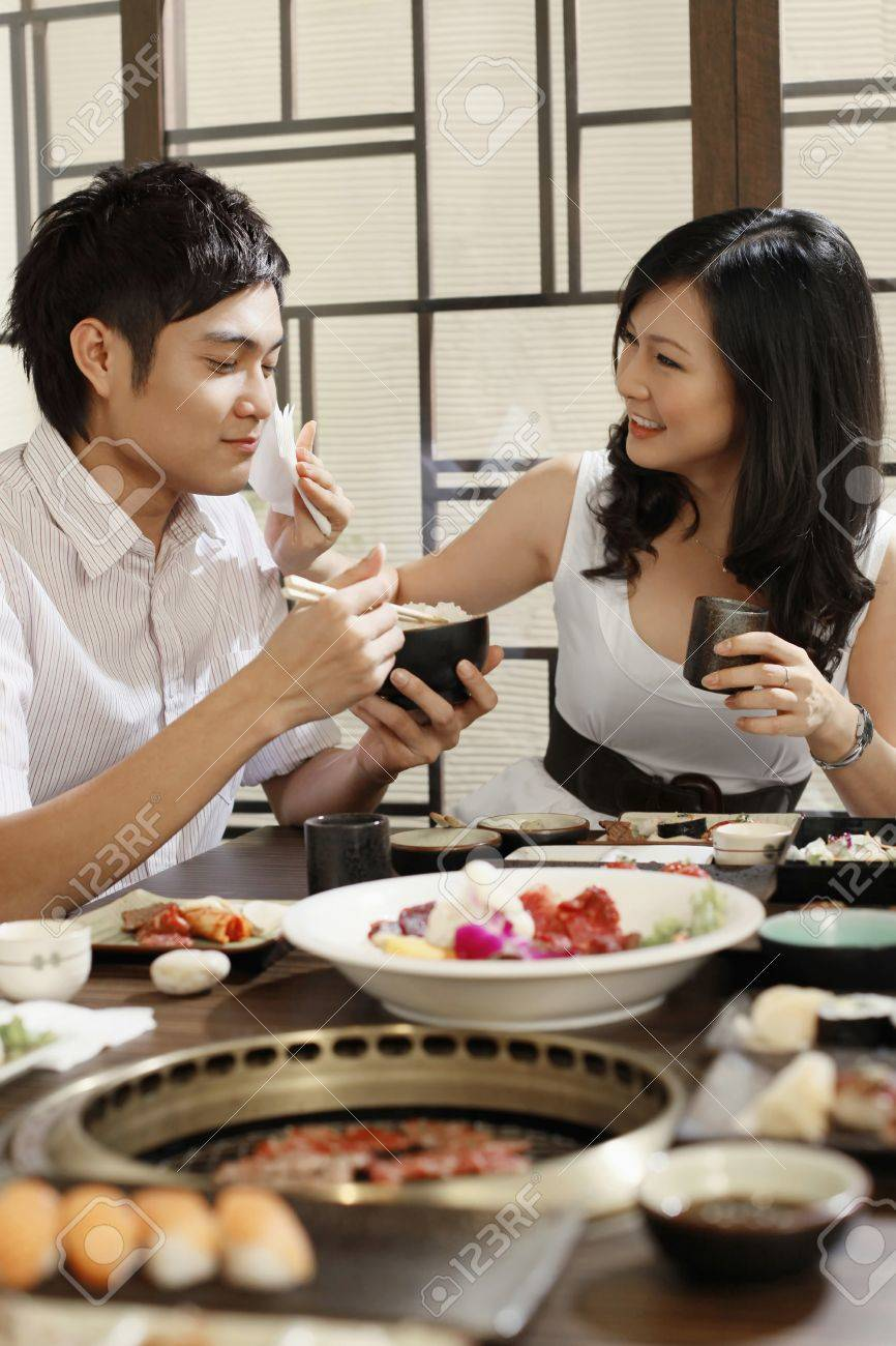 Woman wiping man's mouth while eating in a restaurant Stock Photo - 8148709