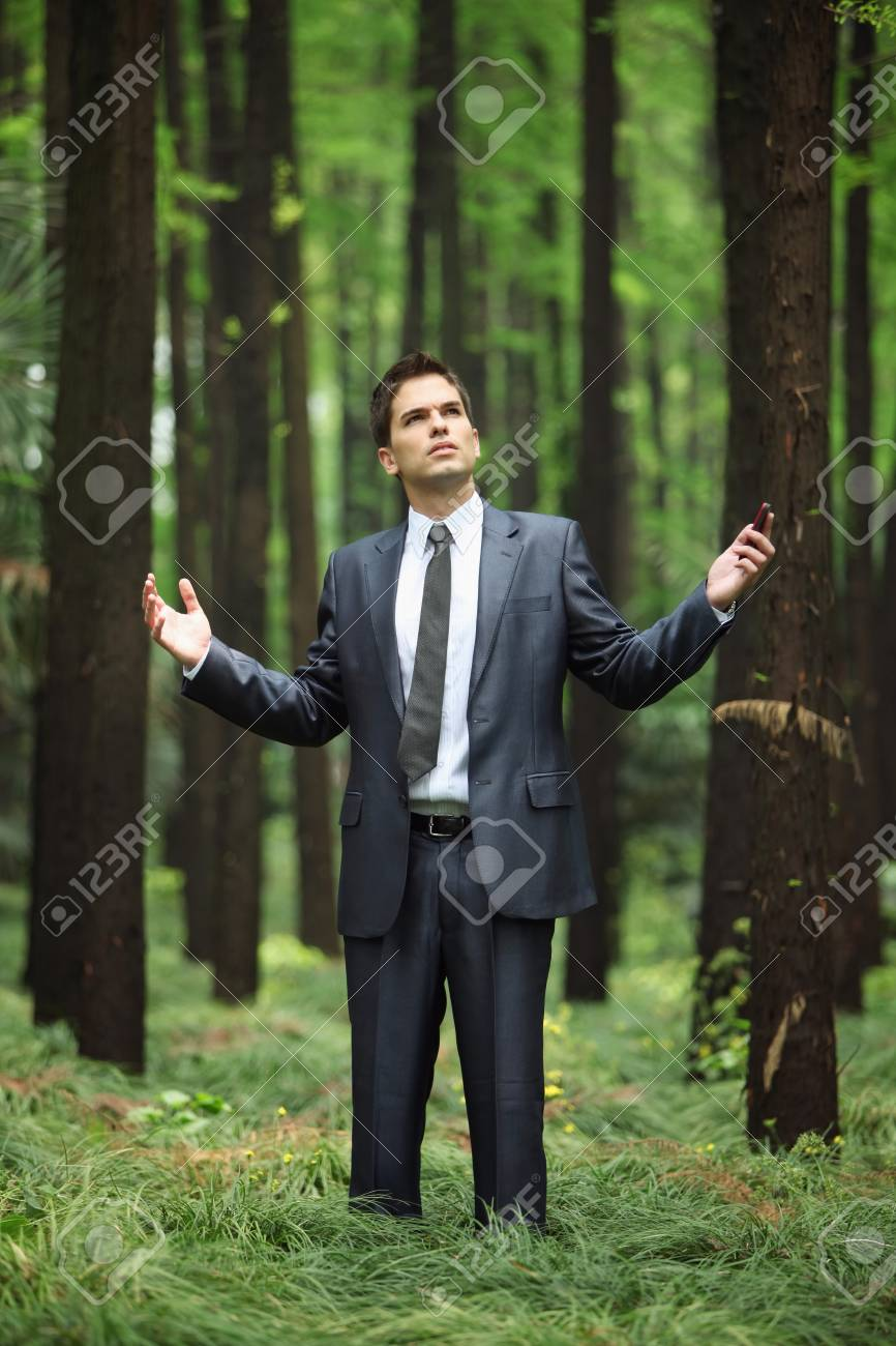 Businessman with mobile phone in forest Stock Photo - 8149087