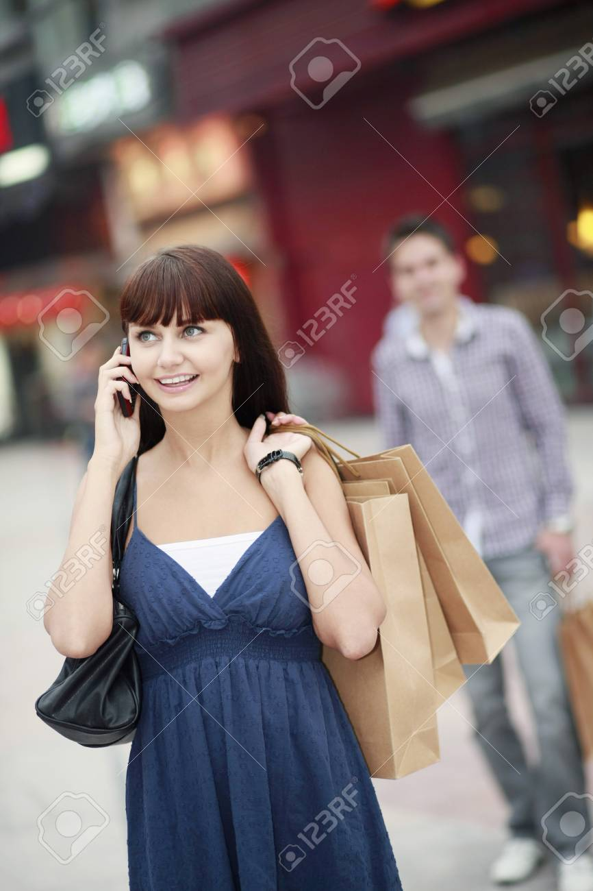 Woman with shopping bags talking on the phone Stock Photo - 8148995
