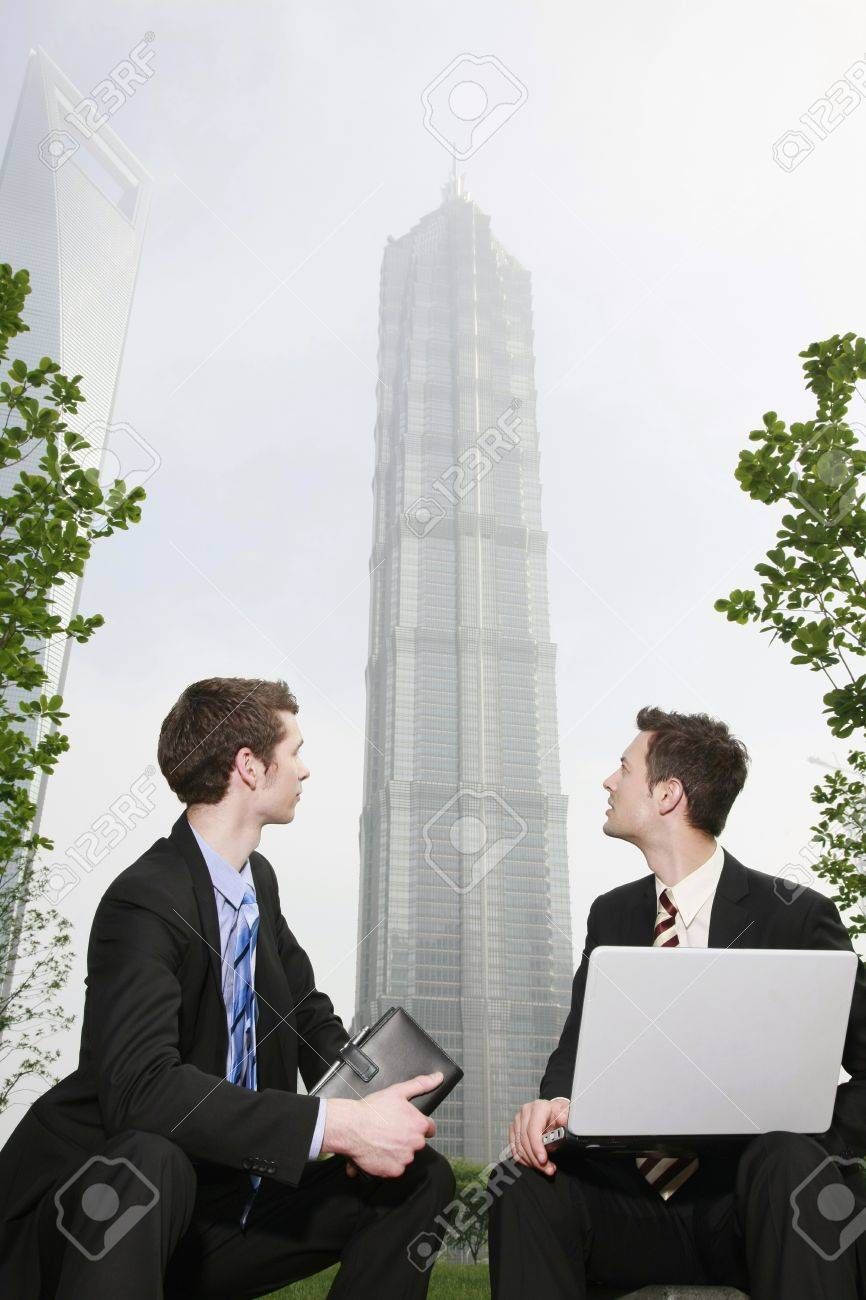 Businessmen looking at skyscraper behind them Stock Photo - 8148800