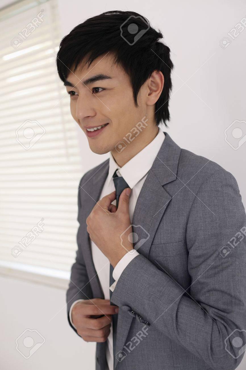 Man adjusting his tie Stock Photo - 8260650