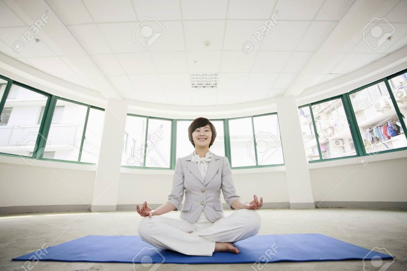 Businesswoman meditating on exercise mat Stock Photo - 8260587