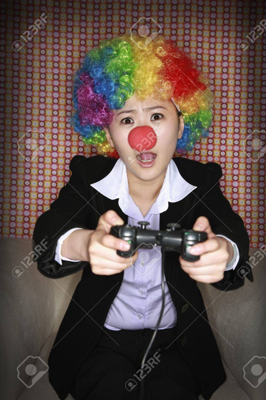 Businesswoman wearing a clown's wig and nose playing video game Stock Photo - 8260605