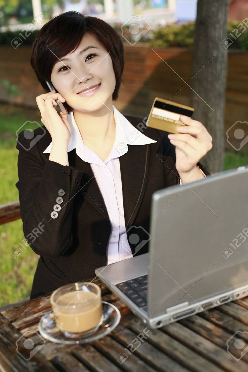 Businesswoman holding credit card while talking on the phone Stock Photo - 8260189