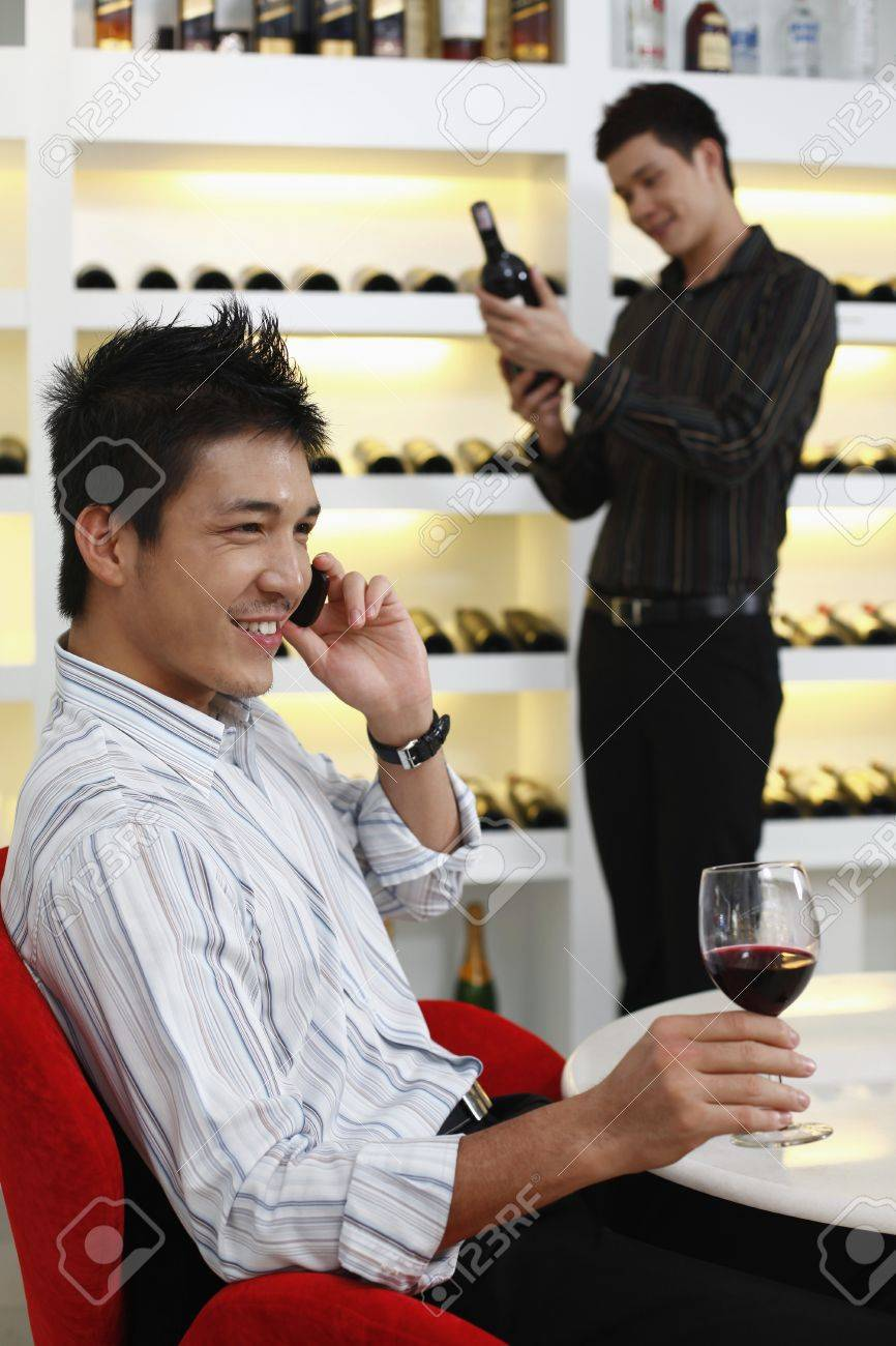 Man talking on the phone, another man is choosing wine in the background Stock Photo - 8458519