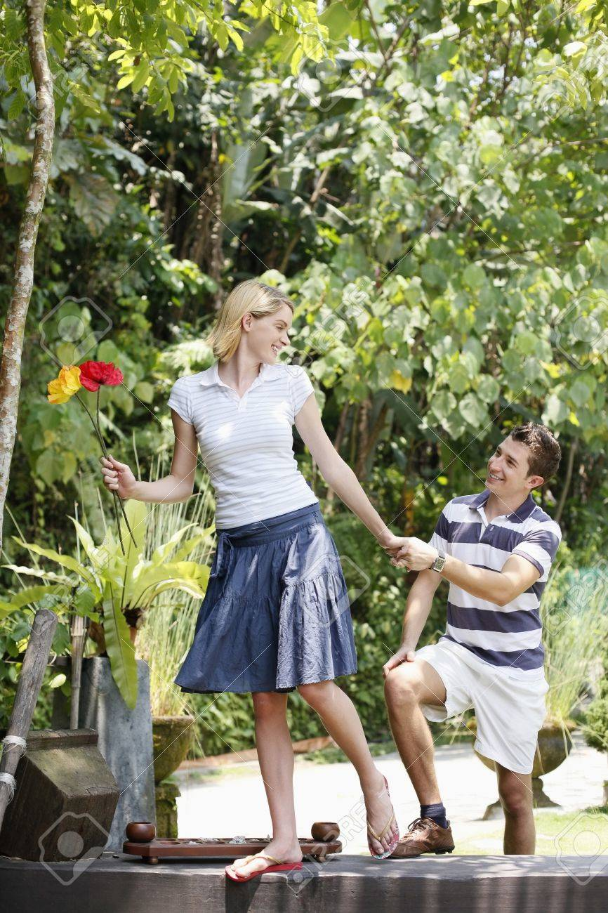 Woman holding flowers, man holding woman's hand Stock Photo - 8606212