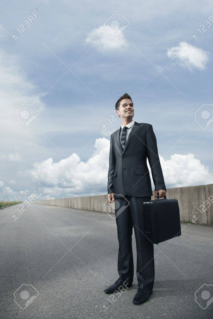 Businessman with bag standing on an empty road Stock Photo - 8981235
