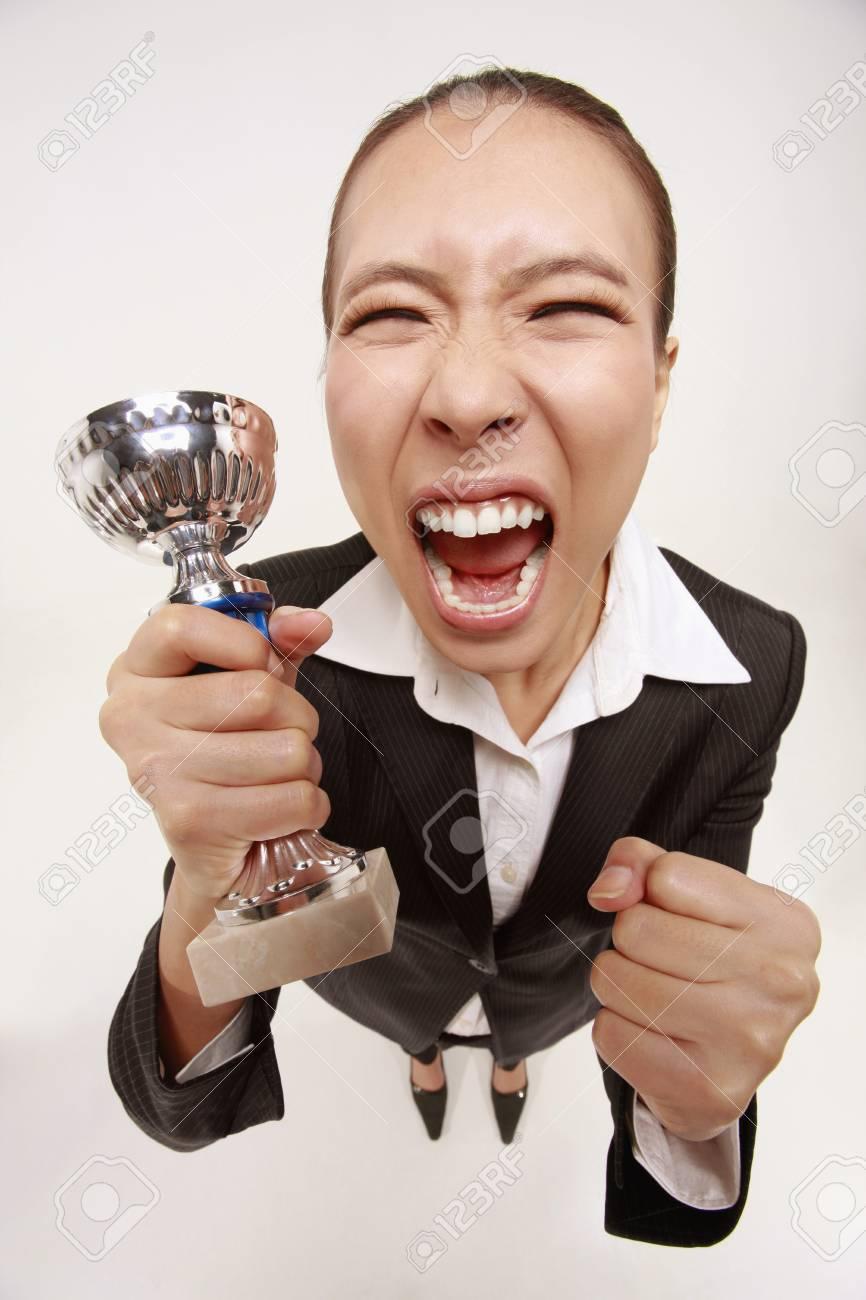 Businesswoman holding trophy, celebrating Stock Photo - 9288057