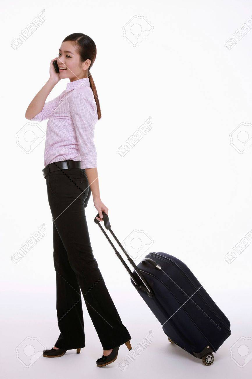 Businesswoman talking on the mobile phone while pulling her luggage Stock Photo - 9520824