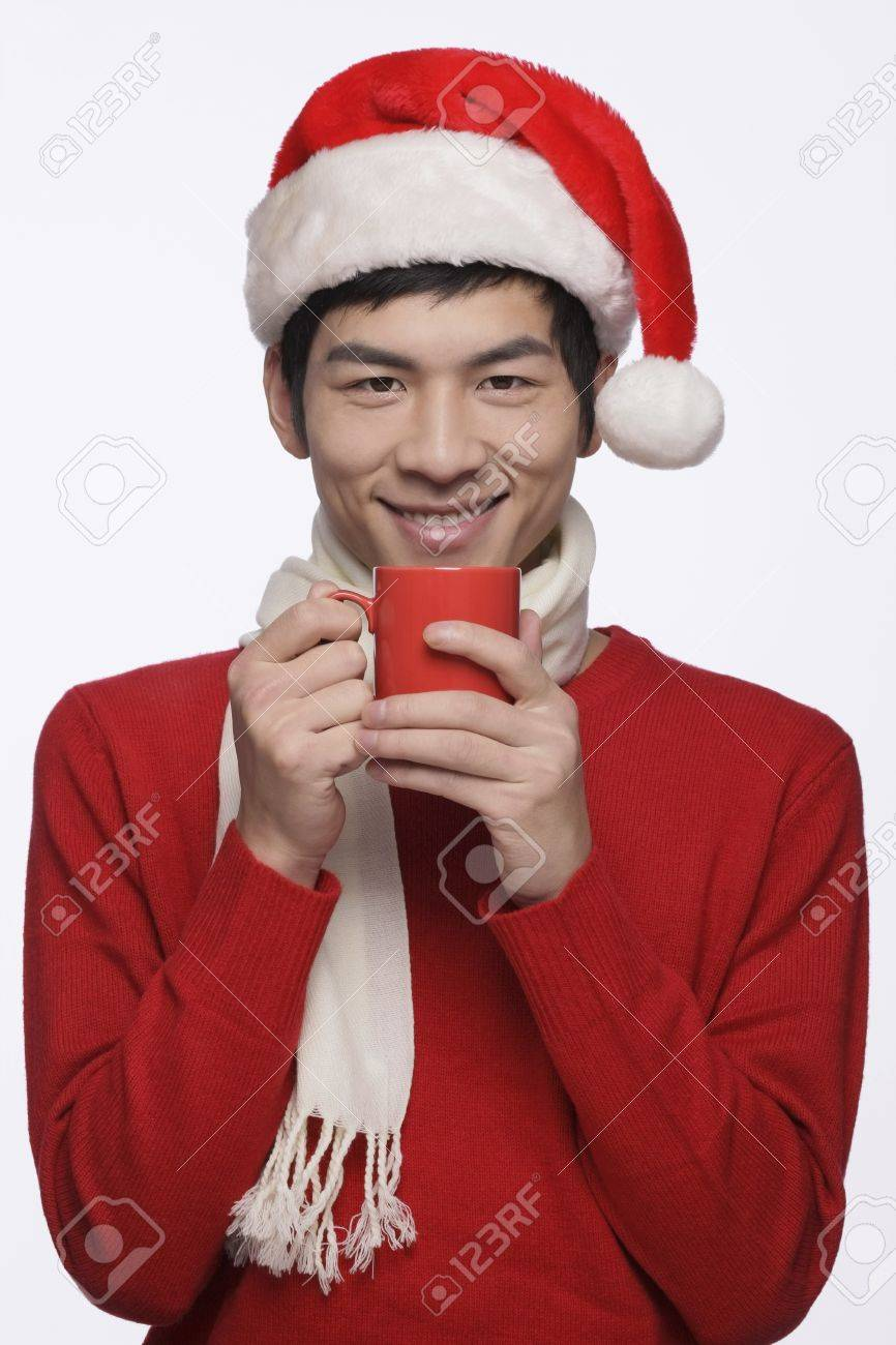 Man with santa hat holding a cup of hot coffee Stock Photo - 9957847
