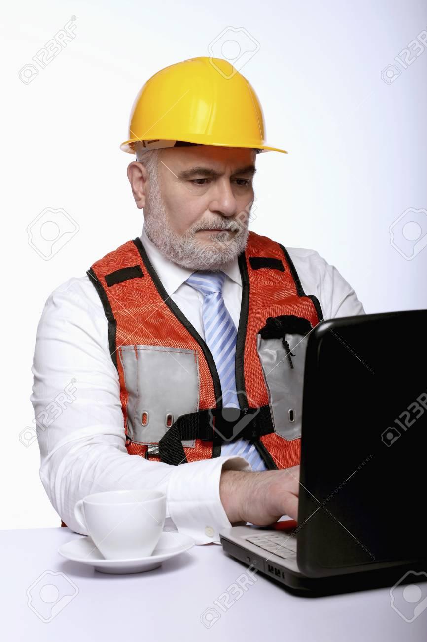 Man with hardhat using laptop Stock Photo - 9957730