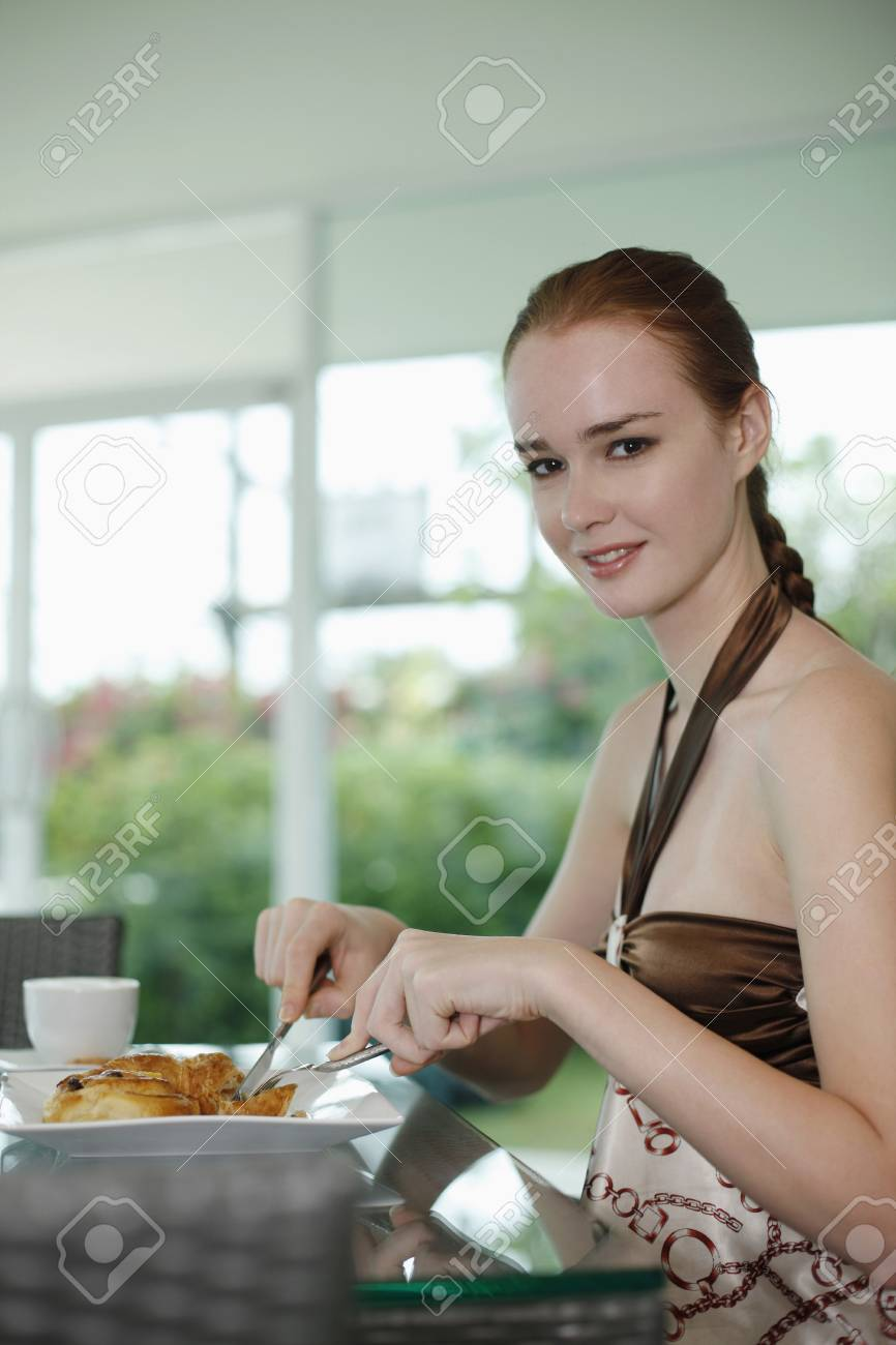 Woman enjoying breakfast of pastry and coffee at bakery Stock Photo - 10571829