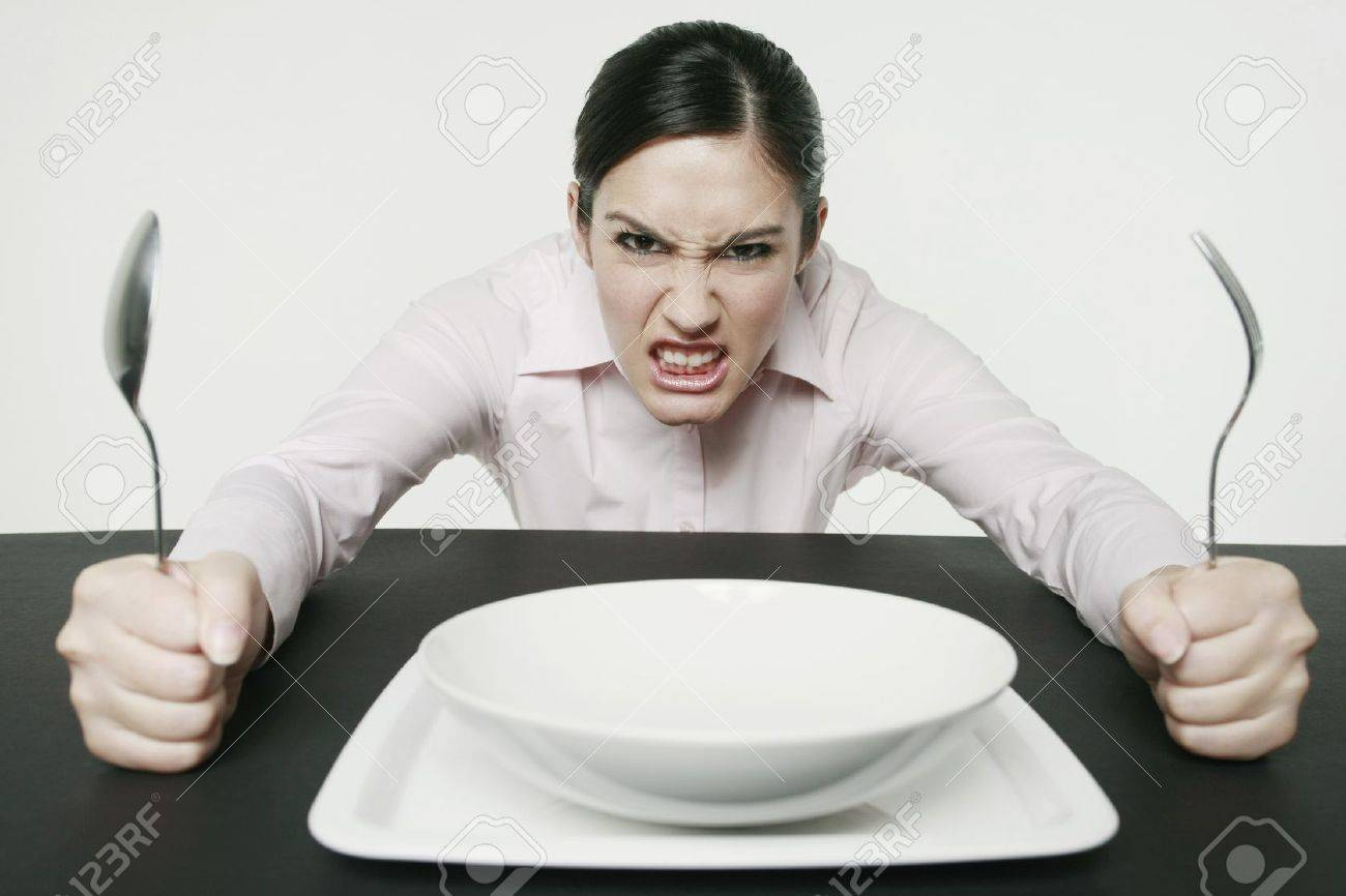 Businesswoman sitting at table looking angry - 10572559