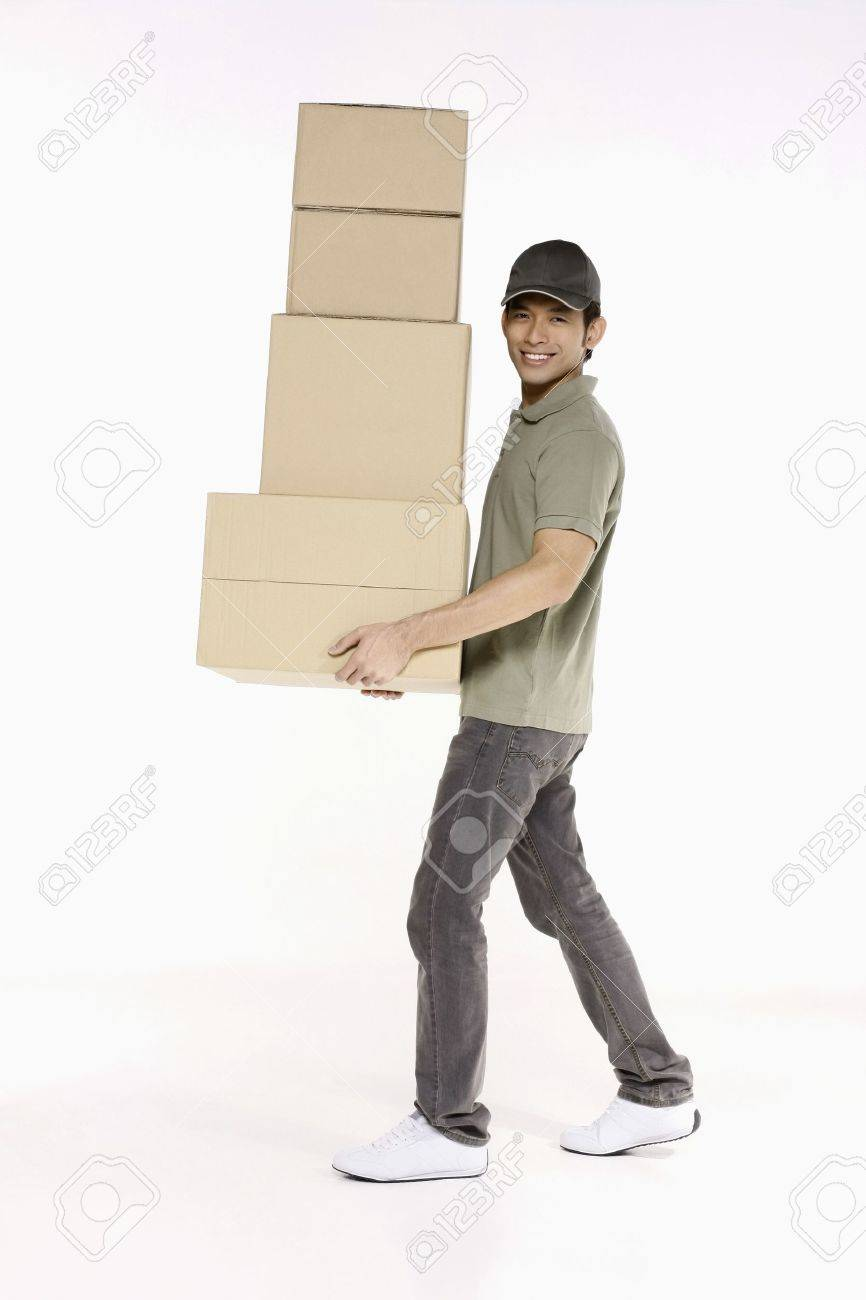 Man carrying a stack of packages - 10862031