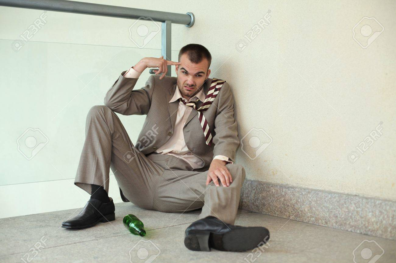 Drunk businessman sitting on the floor pointing at his head - 13355276
