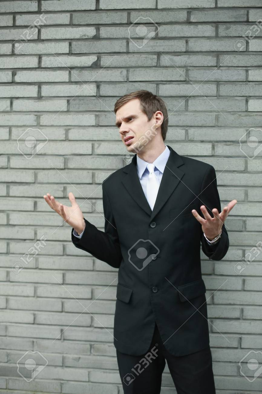 Businessman standing in front of brick wall with arms raised Stock Photo - 13355115
