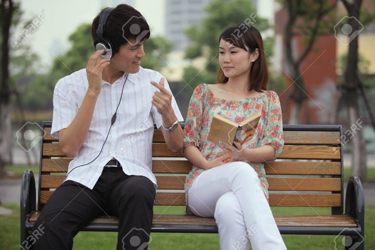 Man listening to music on the headphones, woman reading book on the bench Stock Photo - 13355265