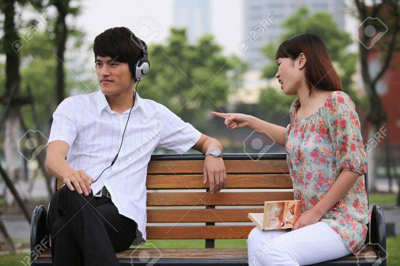 Man listening to music on the headphones, woman scolding man Stock Photo - 13355198