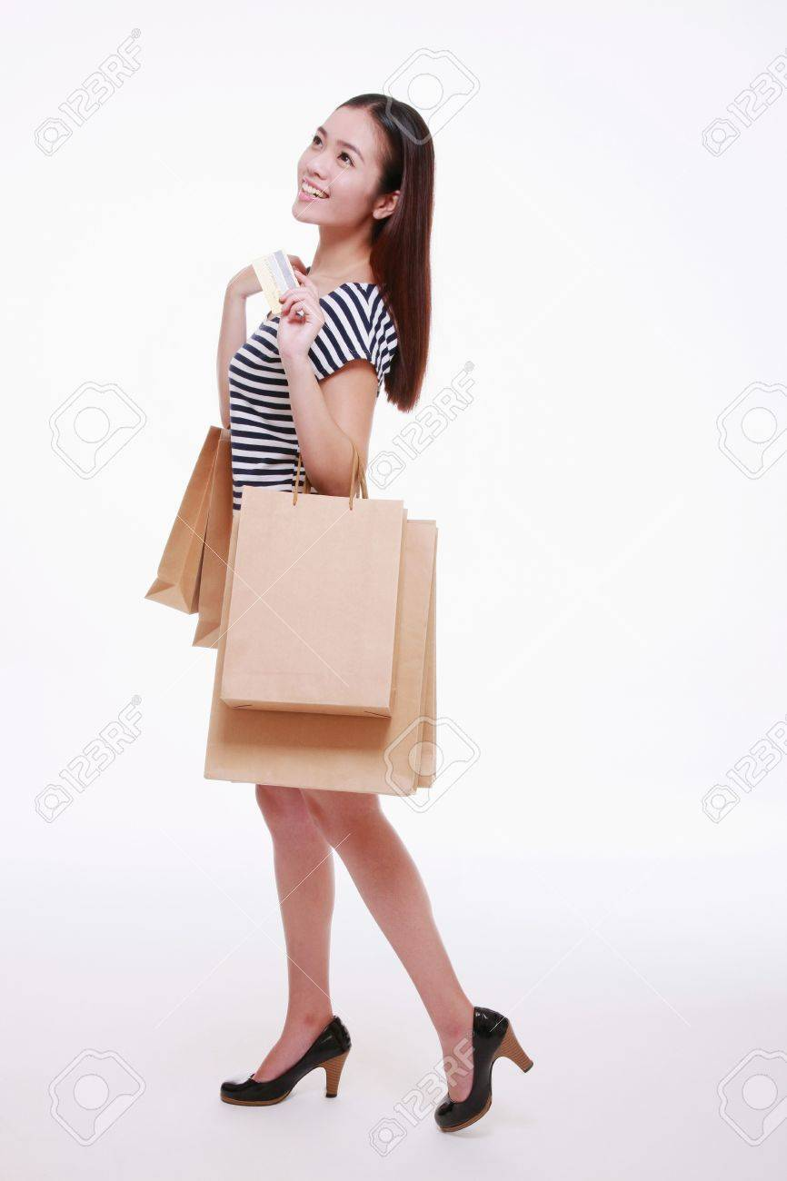 Woman holding credit card and shopping bags - 13443104