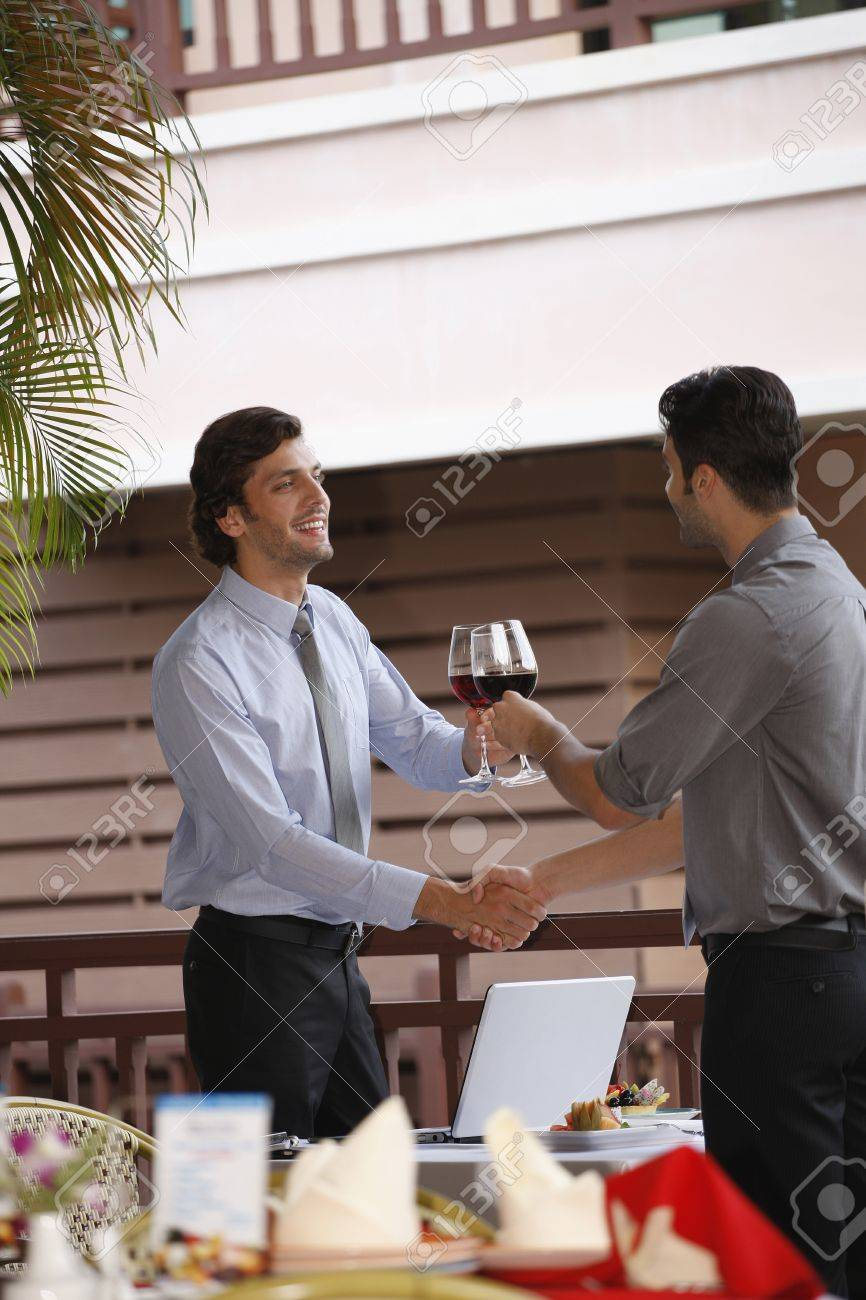 Businessmen shaking hands and toasting red wine Stock Photo - 13377764