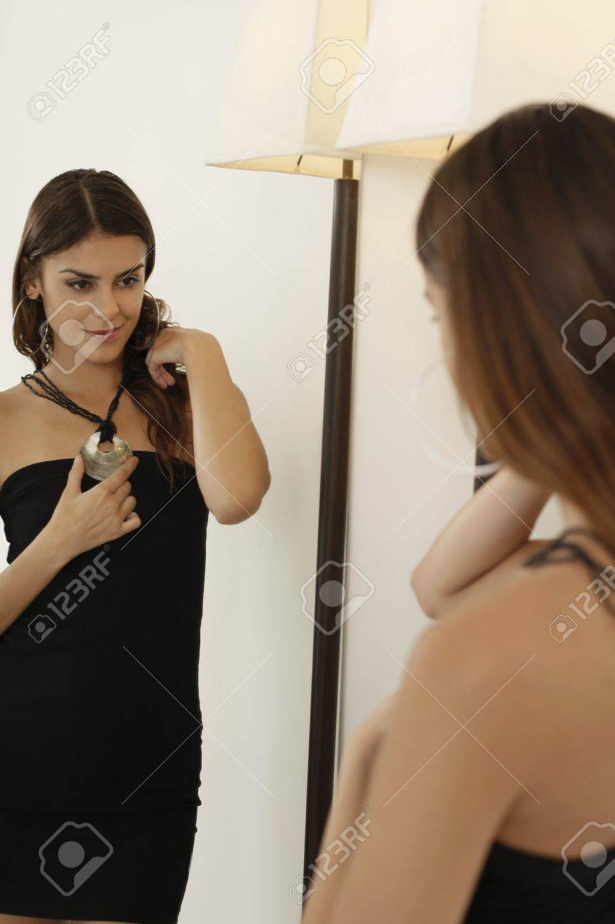 Woman trying on necklace in front of mirror Stock Photo - 13378004