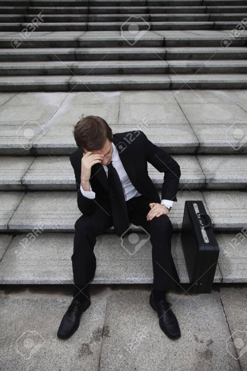 Businessman sitting on stairs looking depressed - 13441096