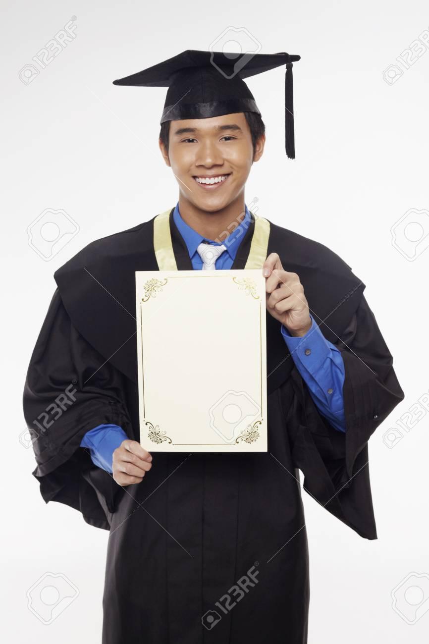 414944679 Foto de archivo - Hombre en traje de graduación celebración certificado en  blanco
