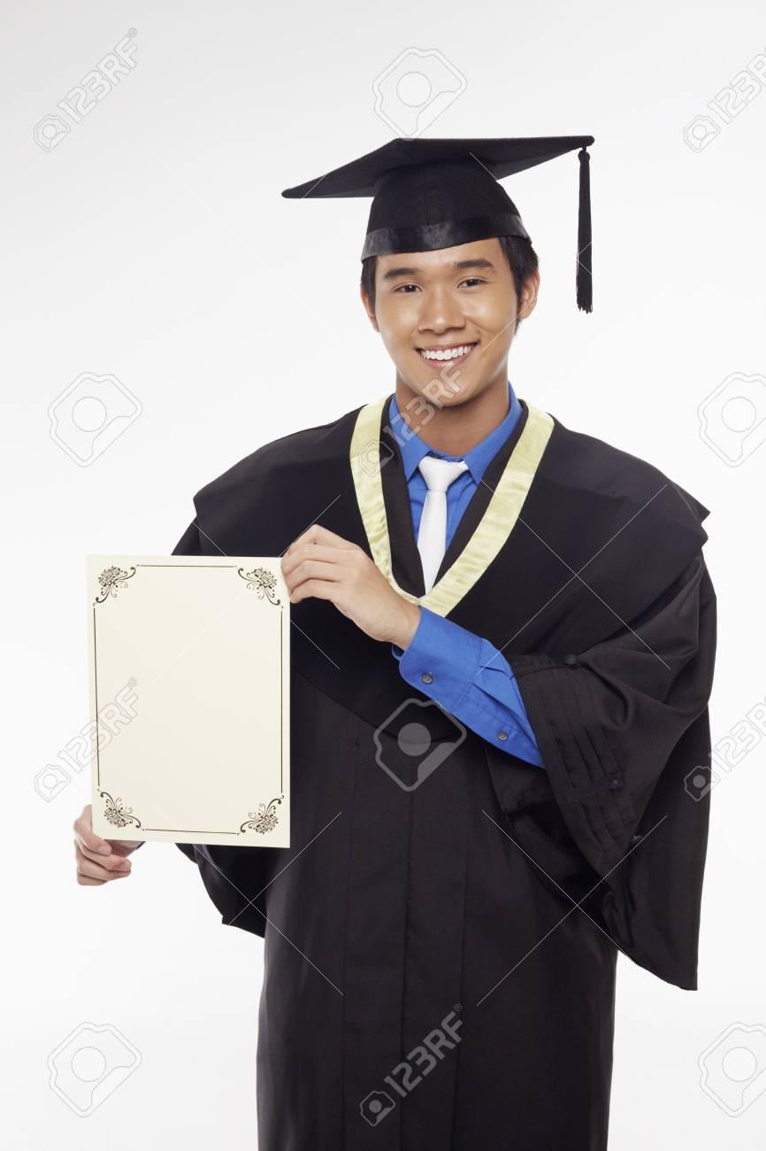 Man in graduation robe holding blank certificate Stock Photo - 17340280