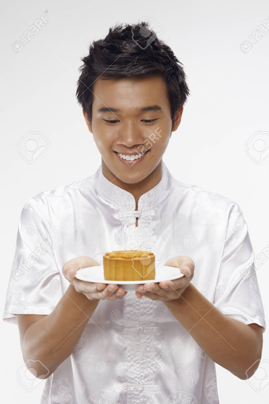 Man in traditional clothing holding mooncake on a plate Stock Photo - 17340327