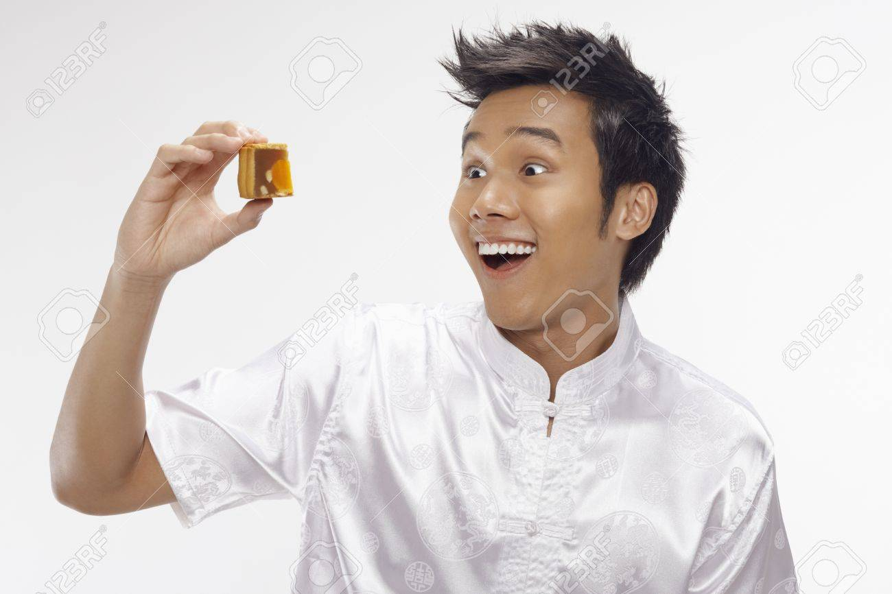 Man holding a piece of sliced mooncake Stock Photo - 17340298