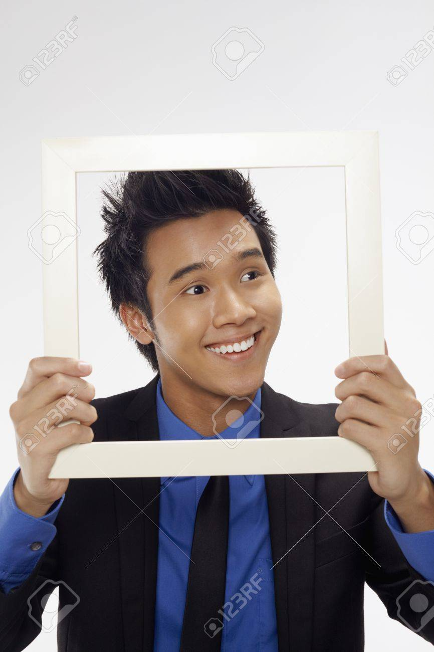 Businessman smiling and looking through cutout paper frame Stock Photo - 17340303