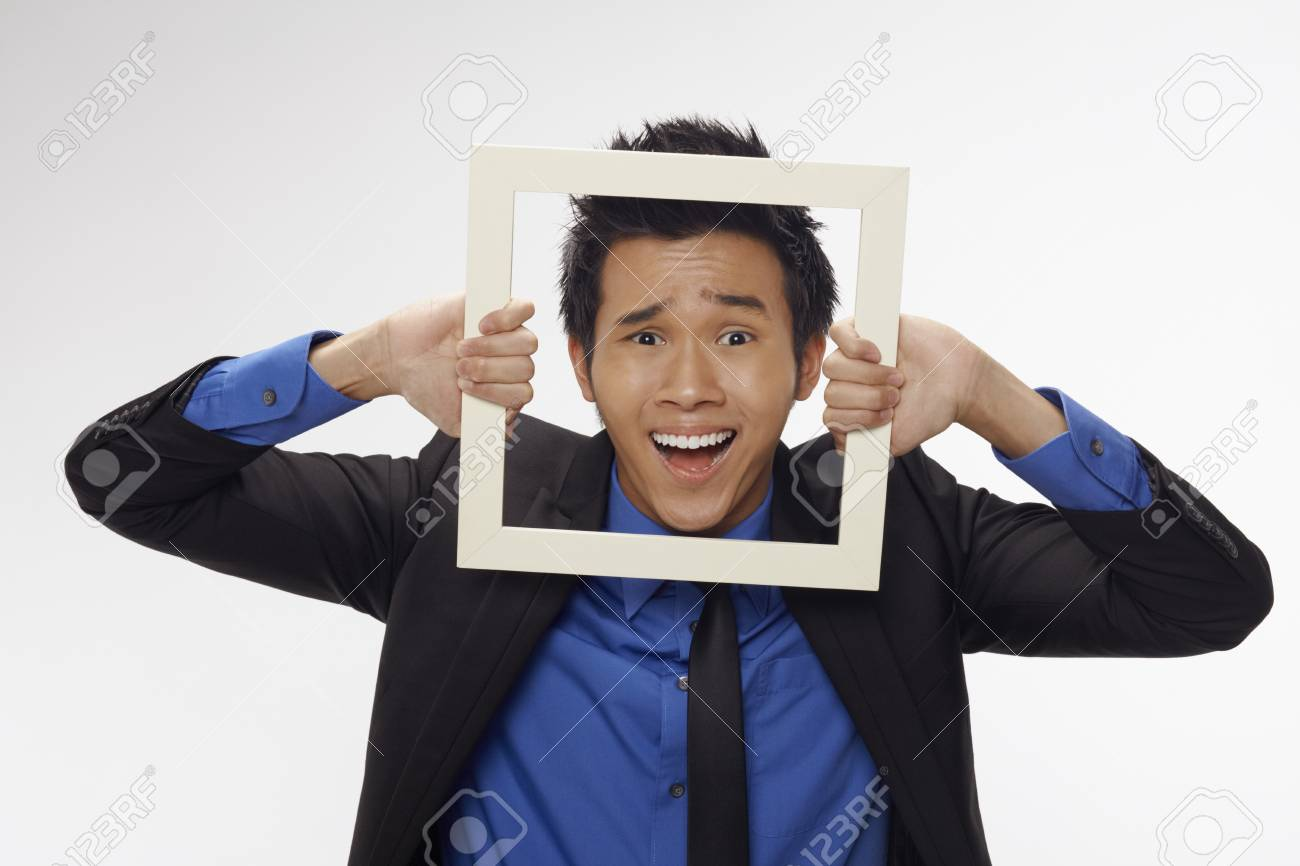 Stressed businessman looking through cutout paper frame Stock Photo - 17340282
