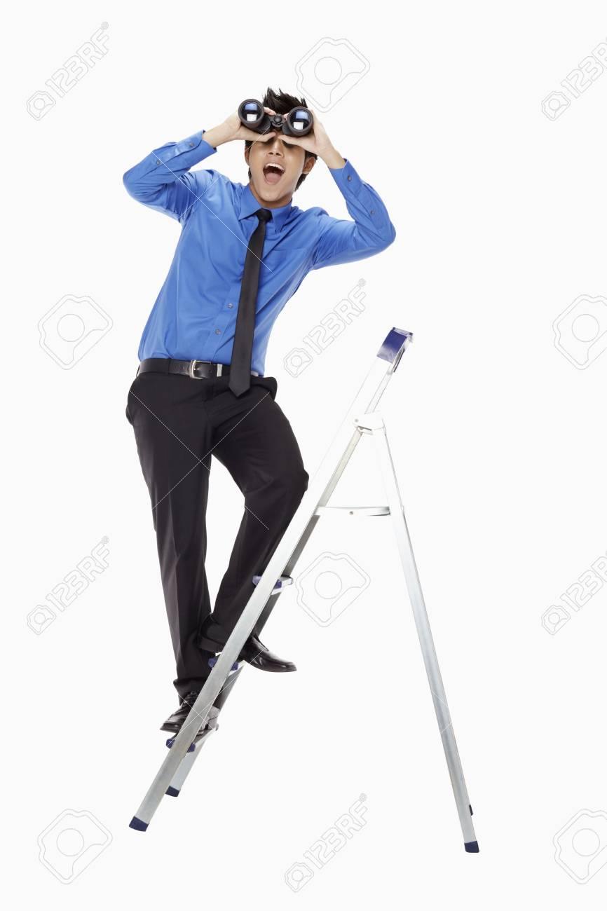 Businessman on ladder looking through binoculars Stock Photo - 17339810