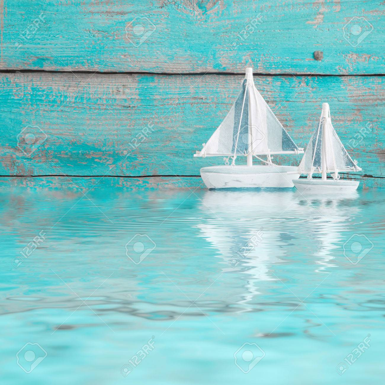 Toy sailboats on the water as a wooden background in turquoise