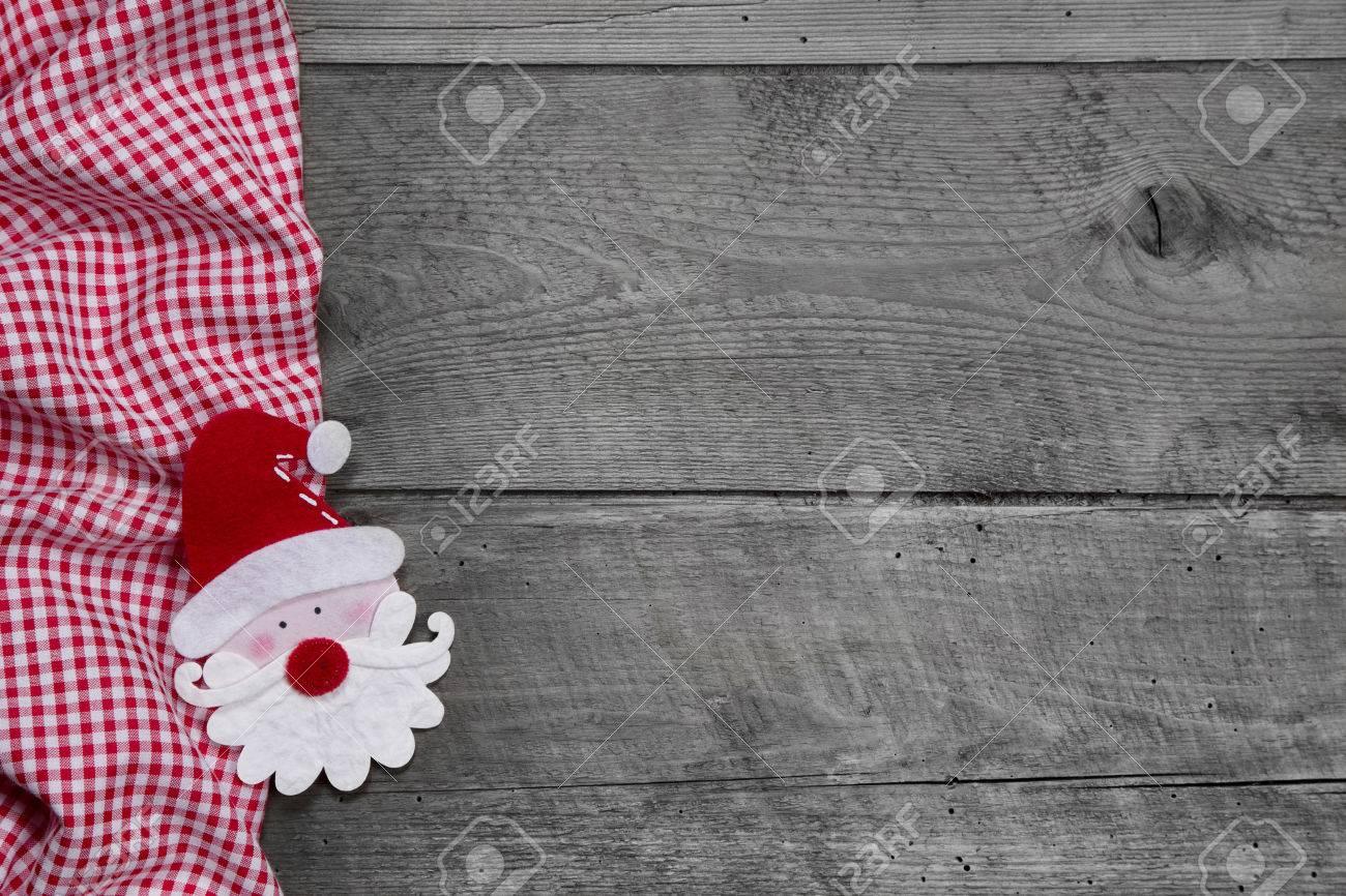 foto de archivo red y tela a cuadros blanco con la cabeza santa en el fondo de madera gris para la navidad