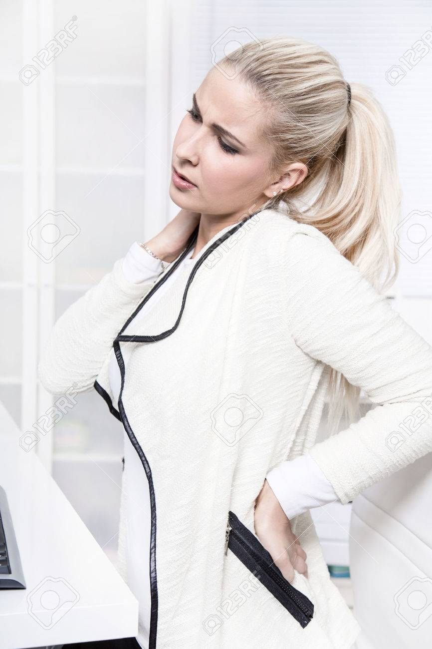 Young beautiful business woman has pains on her back - disc herniation - lack of exercise or not ergonomic work place. Stock Photo - 23759430