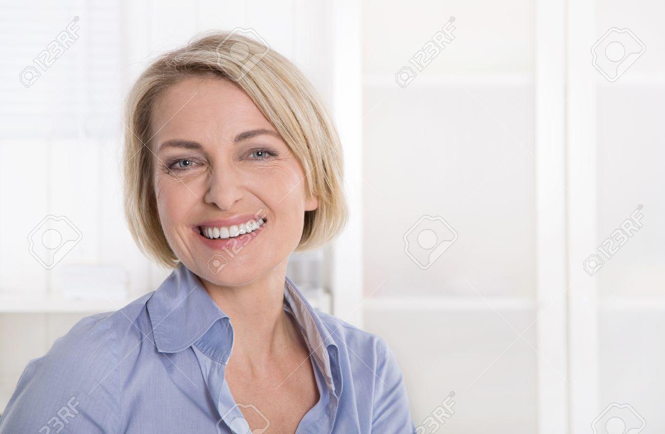 portrait of attractive mature secretary in blue. stock photo