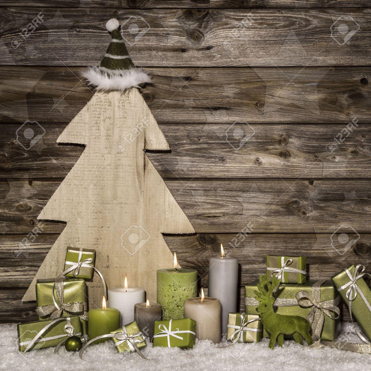 Deco Noel En Bois Naturel décoration de noël naturel en vert et brun sur fond de bois avec des  cadeaux et des bougies allumées.