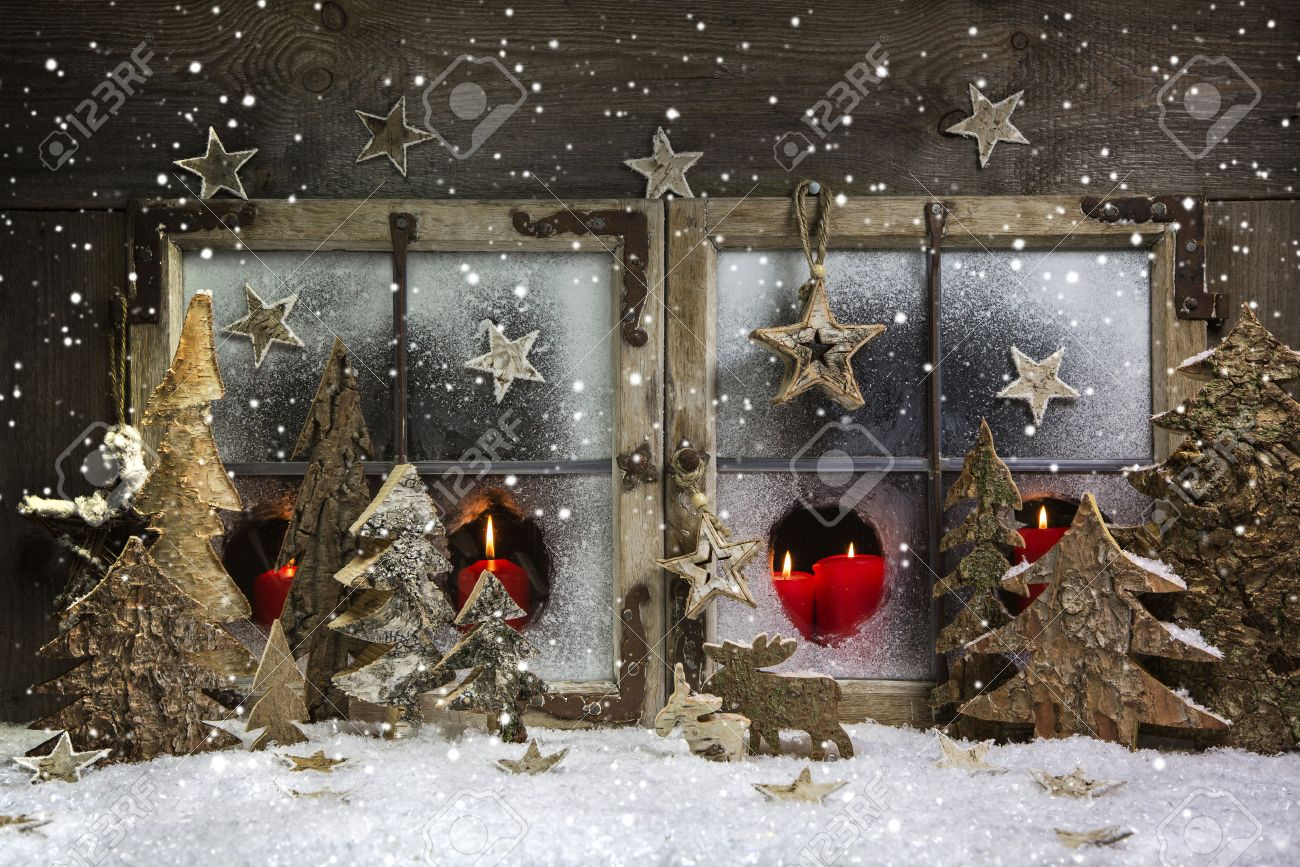 atmospheric and romantic christmas window decoration with red candles snow and wood stock photo