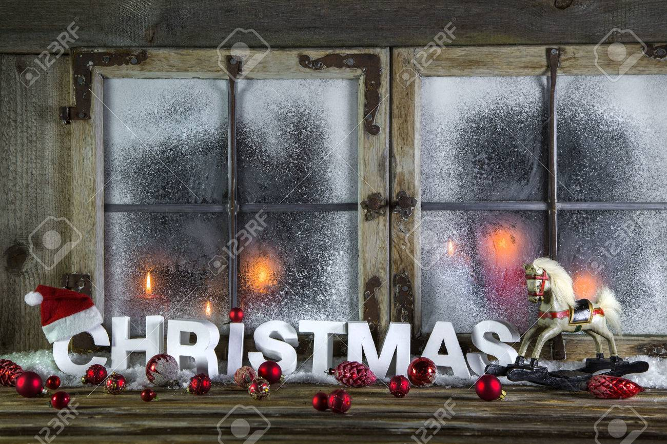 rustic wooden christmas window with red candles horse and greeting text stock photo