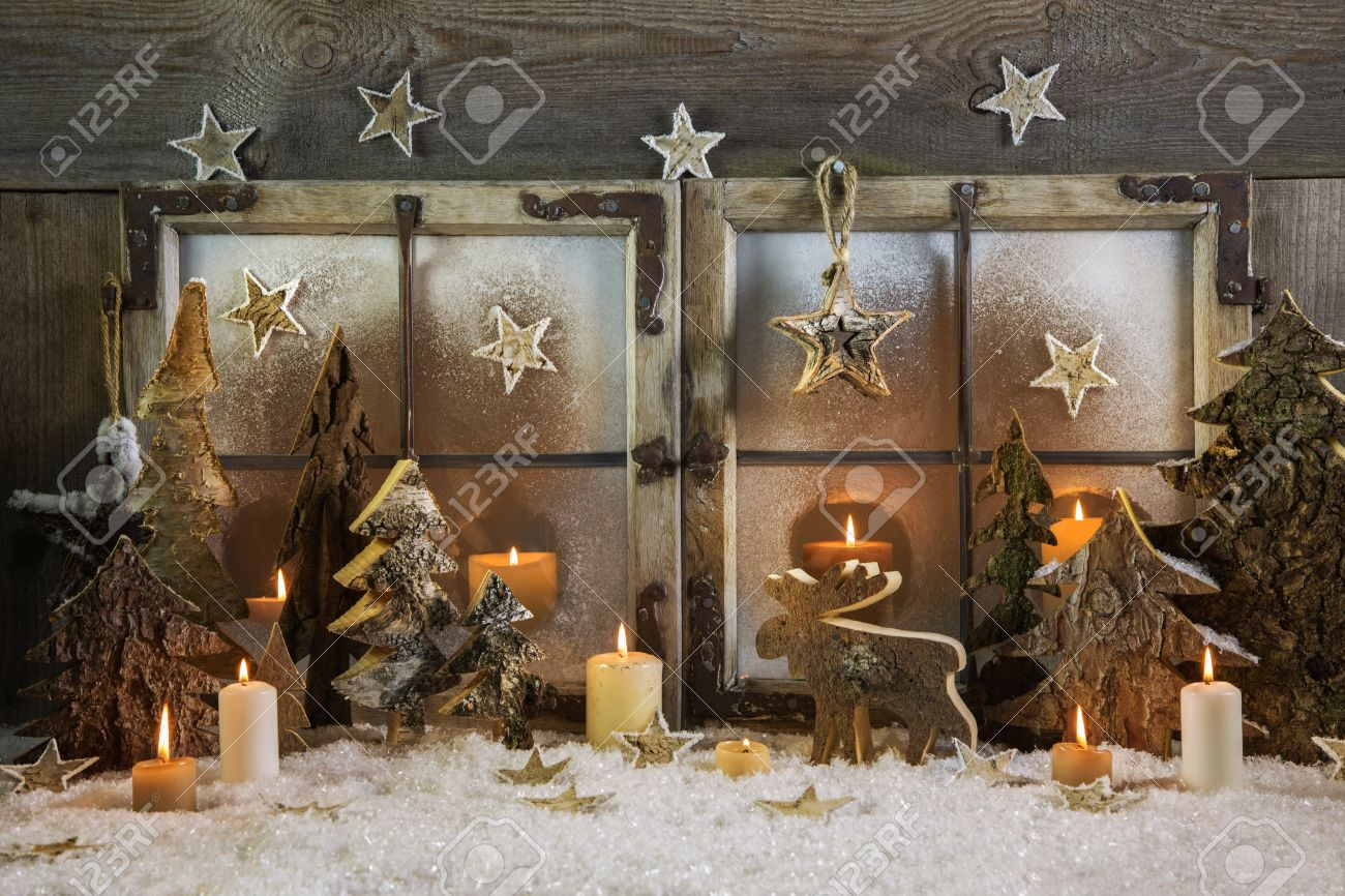 natural handmade christmas decoration of wood outdoor in the window with candles idea for a