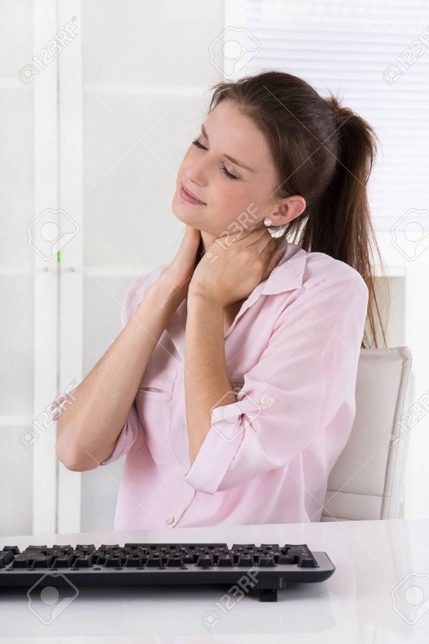 Jeune femme assise dans le bureau ayant douleur dans le cou ou les  ganglions lymphatiques enflés,