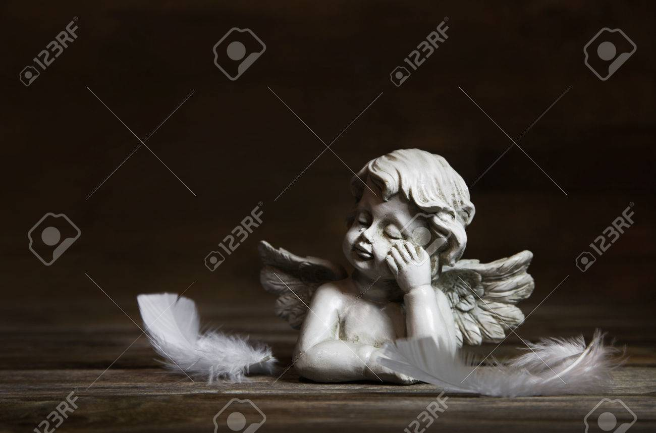 Sad angel with white feathers on a dark wooden background for bereavement. Banque d'images - 34642042