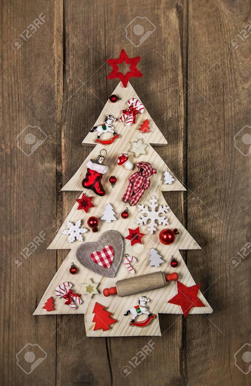 Sapin de Noël fait main en bois dans un style campagnard avec une  décoration blanche et rouge.