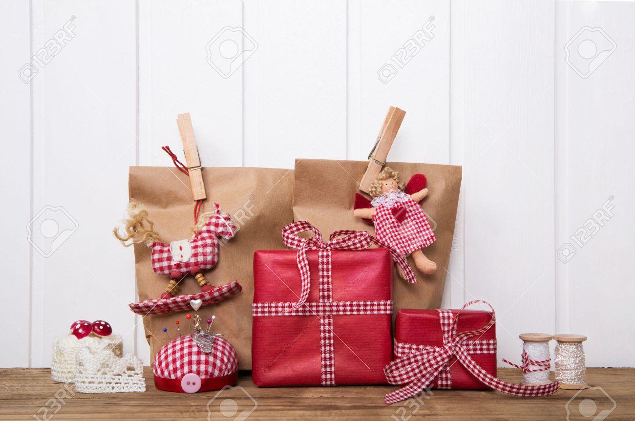 coffrets cadeaux de Noël wripped dans des sacs de papier blanc rouge vérifié ruban, ange, cheval à bascule et fournitures de couture. Banque d'images - 43815084