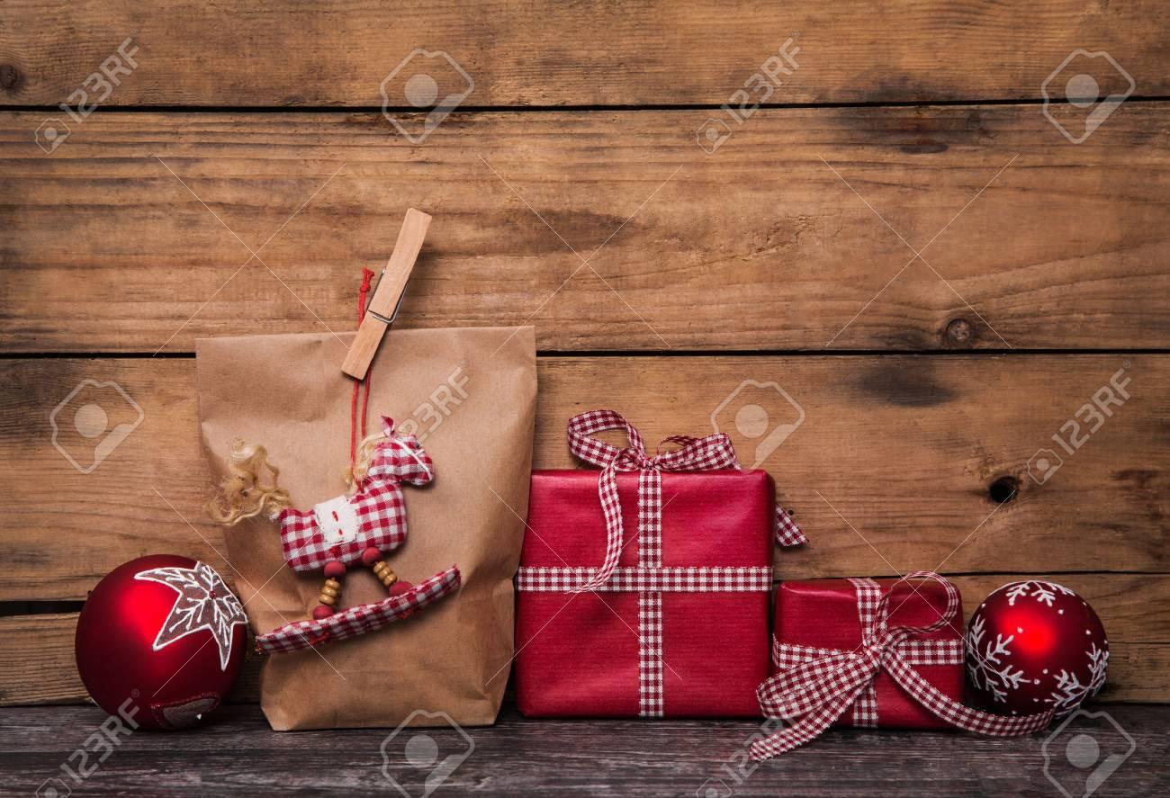 Cadeaux de Noël faits à la main enveloppés dans du papier blanc à carreaux rouges ruban et un cheval à bascule suspendue. Banque d'images - 44397038