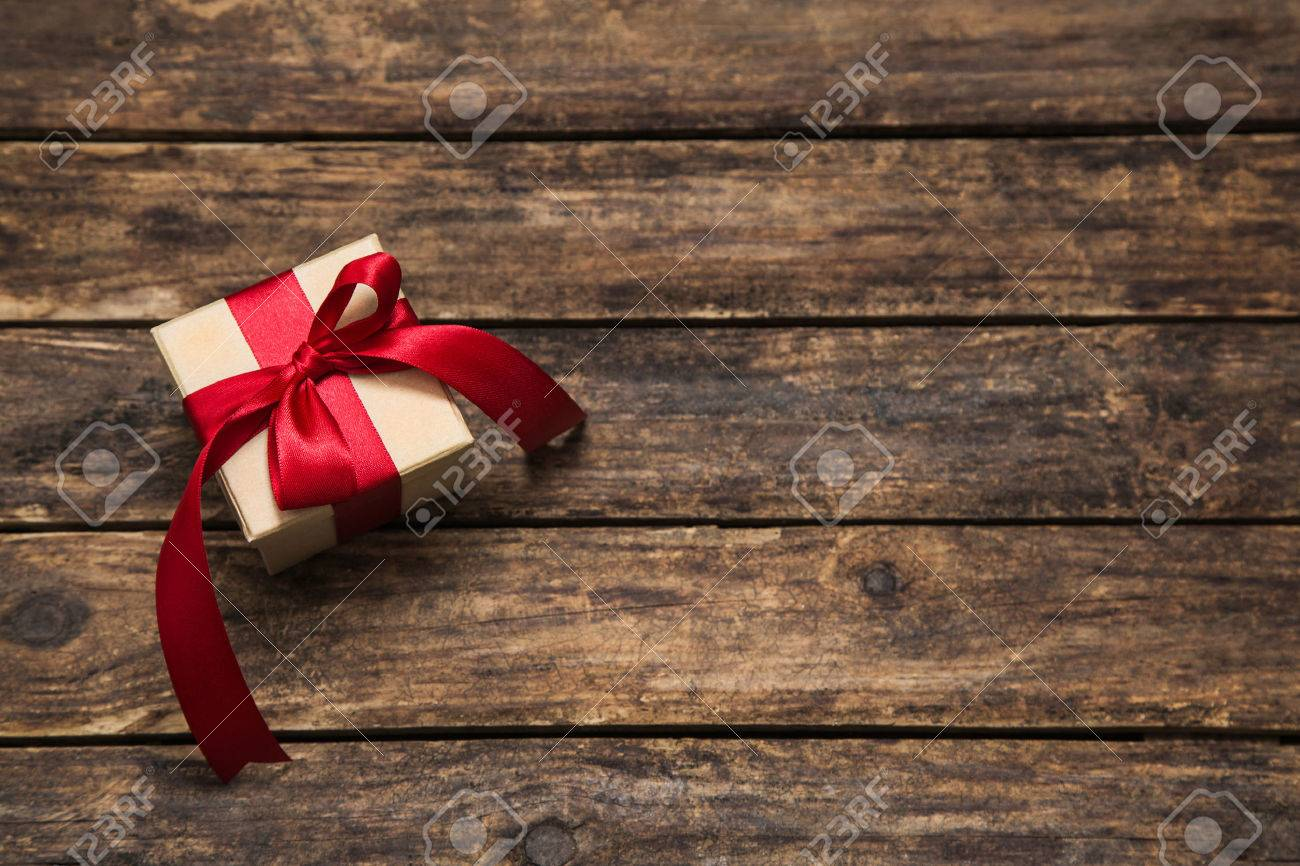 One present with an red big ribbon on old wooden dark brown background for christmas. Banque d'images - 44417447