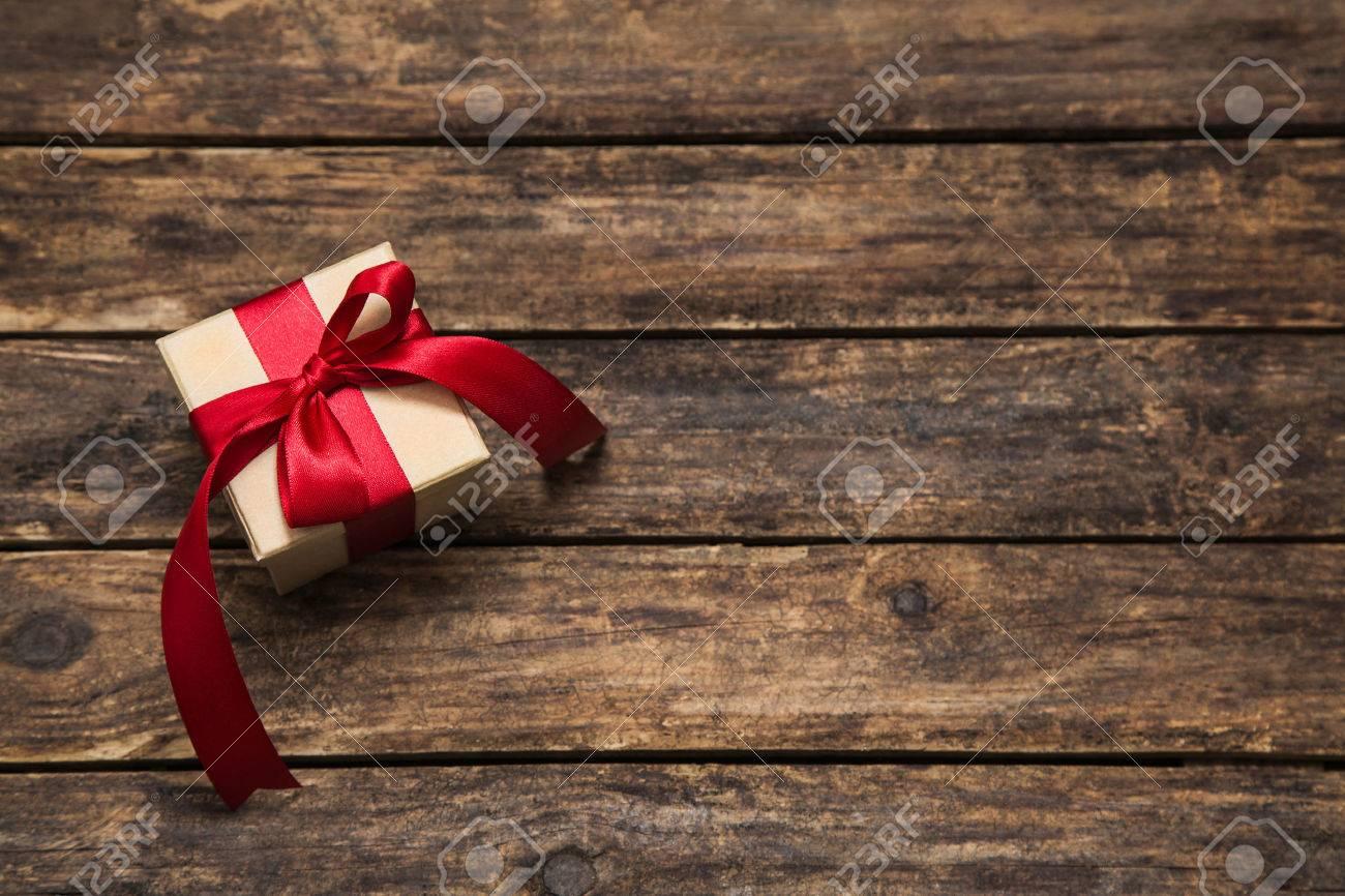 Un présent avec un gros ruban rouge sur le vieux fond de brun foncé en bois pour noël. Banque d'images - 44417447