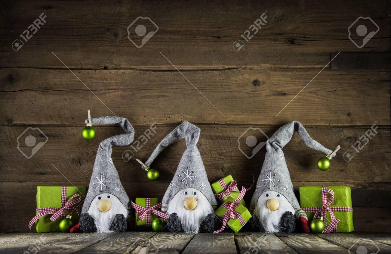 Trois Père Noël avec des chapeaux de feutre gris et Apple cadeaux de Noël verts sur un vieux fond en bois pour la décoration. Banque d'images - 46275127