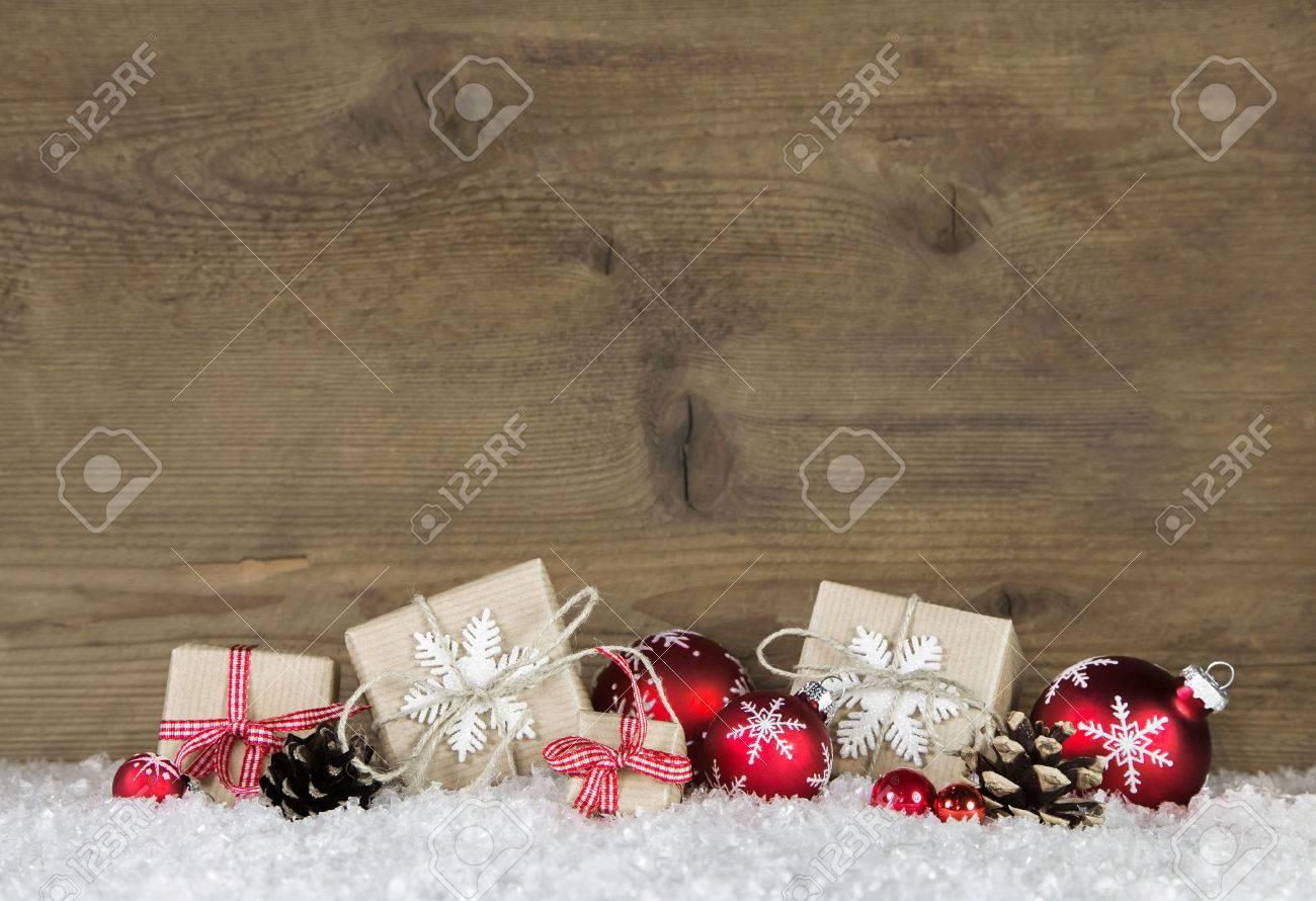 Red cadeaux de Noël enveloppé dans du papier naturel sur le vieux fond gris en bois. Banque d'images - 47341297